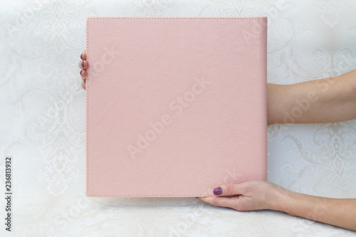 Fotografering  man hold a photo album photobook in the hands a woman holds a photobook sampl