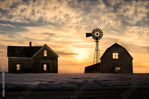 old abandoned silhoetted house and barn with beautiful sunset
