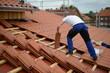 canvas print picture - Dachdecker Bauarbeiter Mann auf Haus beim Ton Dachziegeln decken an der Arbeit