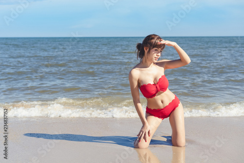 Young woman in bikini enjoying on beach.  Attractive young woman wearing a red bikini kneeling in the surf on a beach.