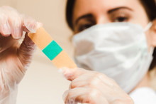Doctor With Mask And Gloves Keeps Plaster Close Up