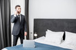 Elegant businessman talking phone near the window in the comfortable hotel room or bedroom