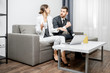 Elegant businessman and woman sitting together on the couch during the work with laptop at home or comfortable office