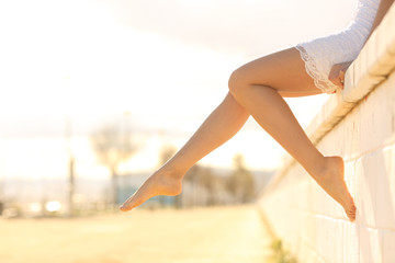 Perfect woman waxed legs outdoors at sunset