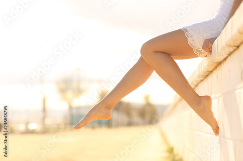 Perfect woman waxed legs outdoors at sunset Poster Mural XXL