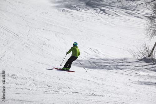 Skier downhill on snowy ski slope at sunny day