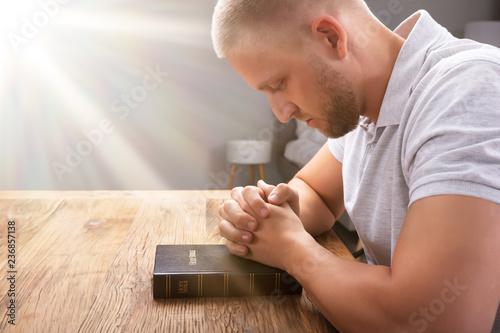 Fotografie, Obraz  Man's Praying Hand On Bible