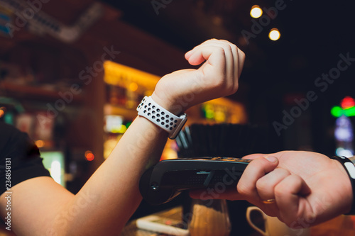 Fototapety, obrazy: Cropped image of female customer paying through smart watch at bar.