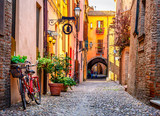 Fototapeta Scene - Cozy narrow street in Ferrara, Emilia-Romagna, Italy. Ferrara is capital of the Province of Ferrara
