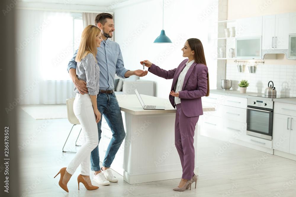 Fototapeta Female real estate agent giving house key to couple indoors