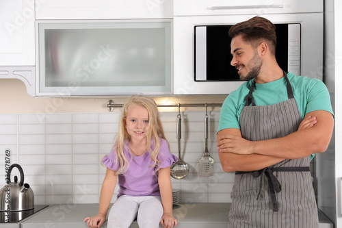 Young man and his daughter near microwave oven in kitchen