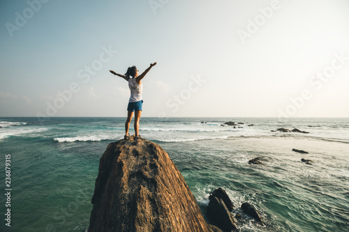 Fotomural  Successful young woman outstretched arms on seaside rock cliff edge