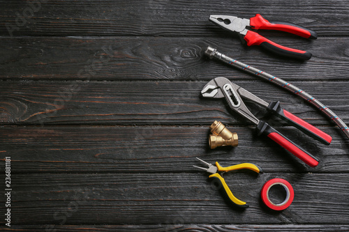 Fotografia  Flat lay composition with plumber's tools and space for text on wooden backgroun