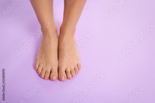 Cuadros en Lienzo Woman with beautiful feet on color background, top view with space for text