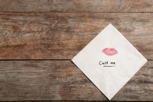 Paper Napkin With Lipstick Mark And Words CALL ME On Wooden Background, Top View. Space For Text