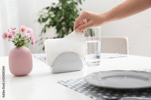 Woman taking paper tissue from ceramic napkin holder on served table