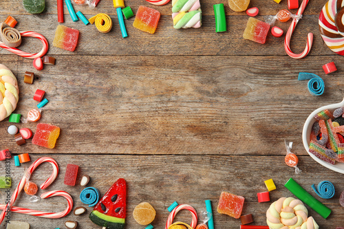 La pose en embrasure Confiserie Flat lay composition with different yummy candies and space for text on wooden background
