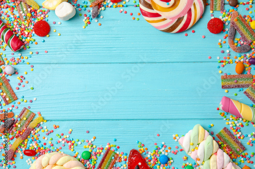 Aluminium Prints Candy Flat lay composition with different yummy candies and space for text on color wooden background