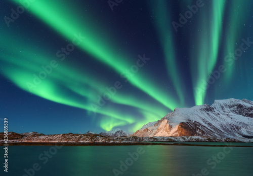 Poster Aurore polaire Aurora borealis above the snow covered mountain in Lofoten islands, Norway. Northern lights in winter. Night landscape with polar lights, snowy rocks, reflection in the sea. Starry sky with aurora