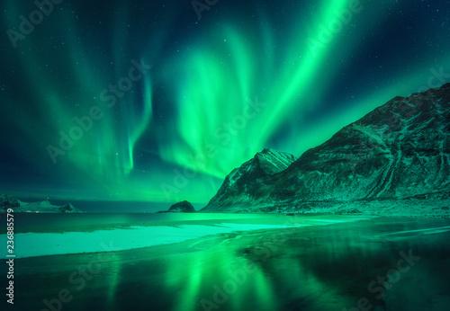 Keuken foto achterwand Noorderlicht Northern lights in Lofoten islands, Norway. Green aurora borealis. Starry sky with polar lights. Night winter landscape with aurora, sea with frosty coast and sky reflection, snowy mountains. Travel