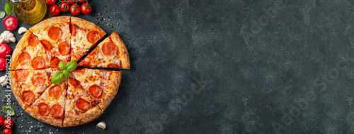 Fototapeta Tasty pepperoni pizza and cooking ingredients tomatoes basil on black concrete background. Top view of hot pepperoni pizza. With copy space for text. Flat lay. Banner obraz