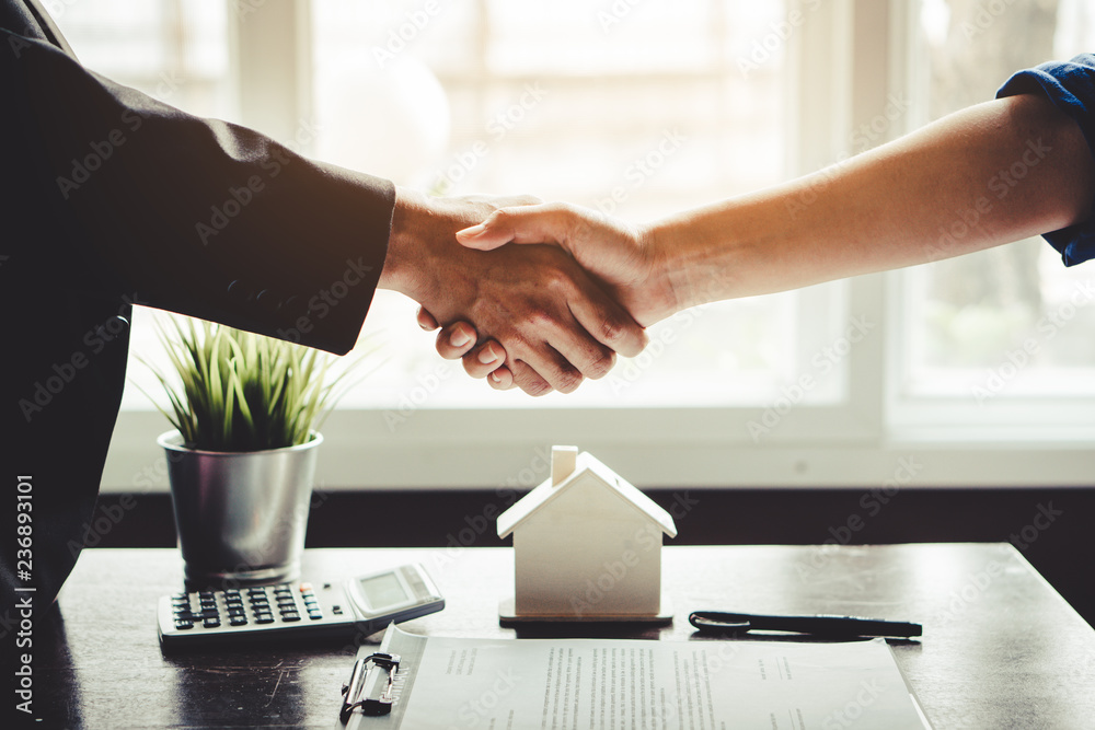 Fototapety, obrazy: The homeowner is happy after receiving the transfer of the right to occupy the home. Agent and client shaking hands after signed document and done business deal for transfer right of property.