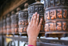 Woman Hand Touching And Spinning Prayer Wheels Of Swayambhunath Stupa In Kathmandu, Nepal