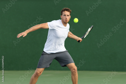 Leinwand Poster Tennis player man hitting ball with racket on green background