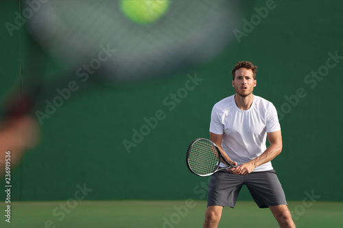 Fotografie, Obraz  Tennis player focused on other player hitting ball with racket on court