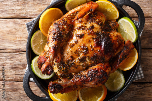 Citrus whole baked chicken served with fresh oranges and limes close-up in a frying pan. horizontal top view