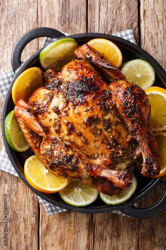 Delicious baked chicken in a spicy citrus marinade close-up in a frying pan. Vertical top view