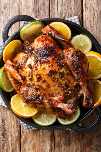 Citrus whole baked chicken served with fresh oranges and limes close-up in a frying pan. Vertical top view