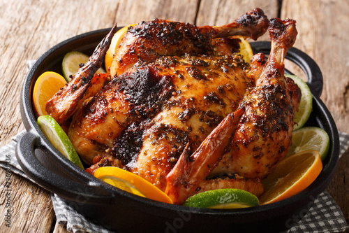 Spicy Cuban Mojo Chicken served with fresh oranges and limes close-up in a frying pan. horizontal