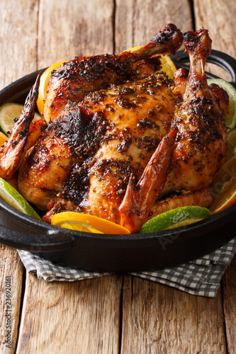 Delicious baked chicken in a spicy citrus marinade close-up in a frying pan. vertical