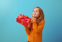 Portrait Of A Little Girl In A Warm Mustard Sweater On A Blue Isolated Background. The Child Looks Dreamily Up And Holds A Red Box With A Gift.The Concept Of Celebration And Receiving A Gift
