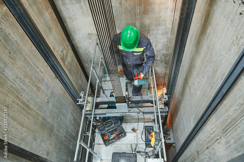 Fototapeta lift machinist repairing elevator in lift shaft obraz