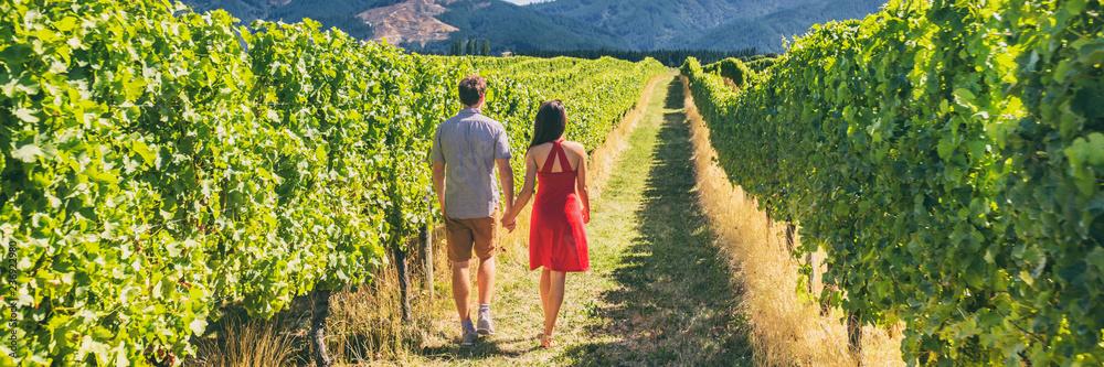 Fototapeta Winery vineyard tourists couple walking on wine farm tour on travel vacation. Wine tasting holiday panoramic banner.