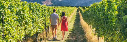 Winery vineyard tourists couple walking on wine farm tour on travel vacation. Wine tasting holiday panoramic banner.