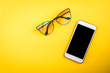 canvas print picture - Mobile phone and glasses on yellow background