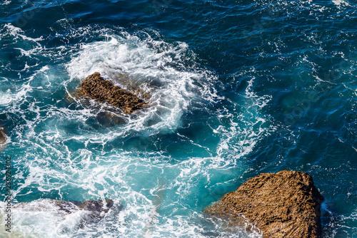 Foto op Aluminium Rivier Sea waves breaking on a rocks. Deep blue sea waves hit cliff, hit rocks cliff. Mighty sea waves breaking on a cliff, splashing over rocks. Strong ocean waves hitting rocks