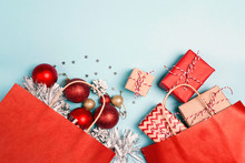 Red Shopping Bags With Christmas Decoration And Gifts  On A Blue Background.
