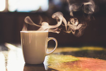 Close Up Of Steaming Cup Of Coffee Or Tea On Vintage Table - Early Morning Breakfast On Rustic Background