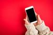 Leinwanddruck Bild - Mobile phone in female hand on red background.