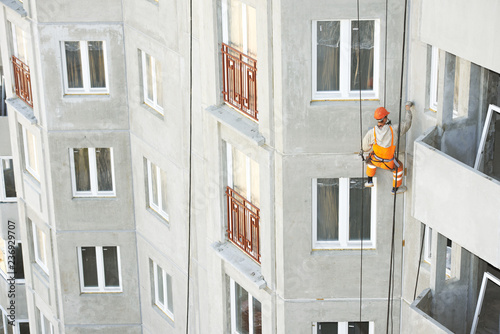 industrial climber. Builder sealing outside facade building seam joints with insulation mastic