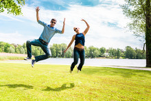 Cheerful Handsome Man And Beautiful Woman Jumping High With Joy In Outdoor Park During A Bright Sunny Day