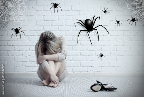 Woman sitting on the floor and looking on imaginary spider. Fototapet