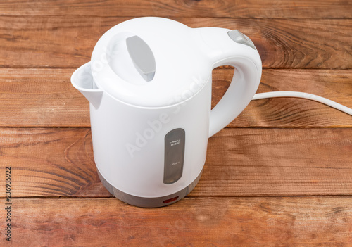 Small white plastic electric kettle on an old wooden table