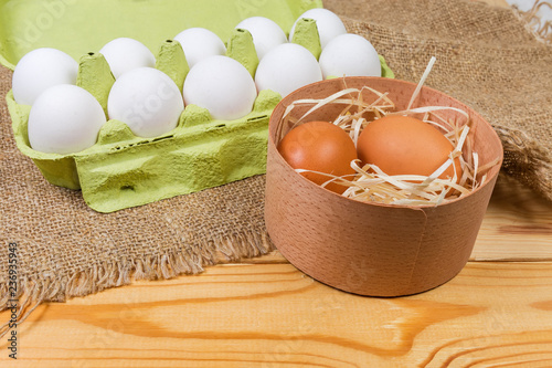 Different chicken eggs in wooden box and paper pulp carton