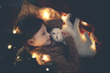 Child Girl And White Cat Under Christmas Tree Real
