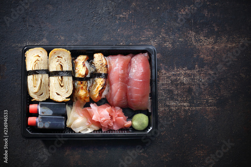 Fototapeta Sushi. Tacka z kawałkami sushi , imbirem , wasabi i sosem sojowym na ciemnym tle. obraz